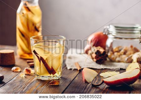 Glass of Water Infused with Sliced Pear Cinnamon Stick Ginger Root and Some Sugar. Ingredients on Wooden Table and Bottle of beverage on Backdrop.