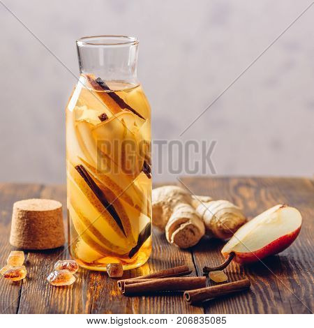Bottle of Water Infused with Sliced Pear Cinnamon Stick Ginger Root and Dark Sugar. Copy Space.