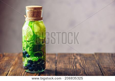 Bottle of Detox Water Infused with Lime Mint and Blueberry. Copy Space on the Right.