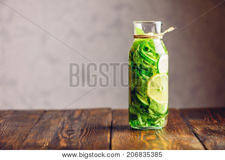 Detox Water Infused with Sliced Lemon Cucumber and Fresh Sprigs of Mint. Copy Space on the Left.