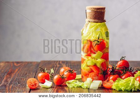Cleansing Water Infused with Celery Stems and Cherry Tomatoes. Ingredients Scattered on Wooden Table. Copy Space on the Left.