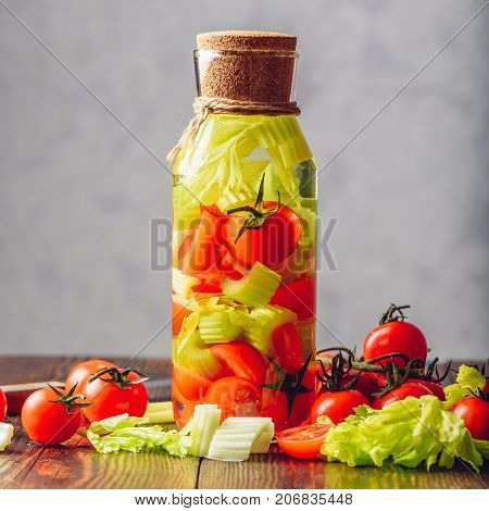 Cleansing Water Infused with Celery Stems and Cherry Tomatoes. Ingredients Scattered on Wooden Table.