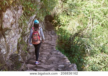 Woman walking on inca trail view from back. Girl with backpack on hiking path