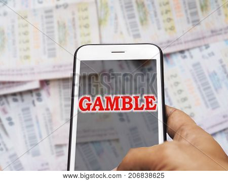 Online gambling concept.Human hand holding mobile phone with red word Gamble on screen display over blurry Thai lottery ticket background.