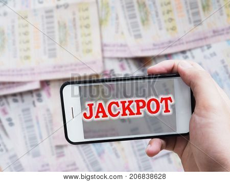 Online gambling concept.Human hand holding mobile phone with red word Jackpot on screen display over blurry Thai lottery ticket background.