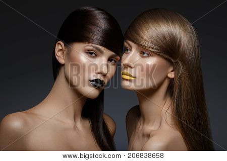 two beautiful young women with black and yellow lips and shiny healthy hair. beauty shot on black background. copy space.