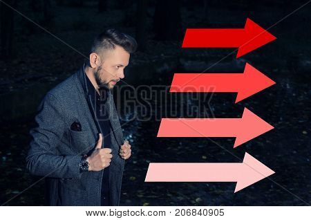 stern bearded man in an aggressive pose with his hands on lapels of his jacket