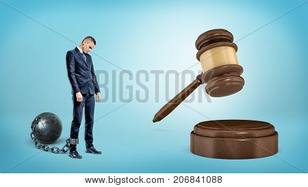A small sad businessman leashed to an iron ball stands near a giant hitting judge gavel. Business law. Bureaucracy restrictions. Corporate lawsuit.