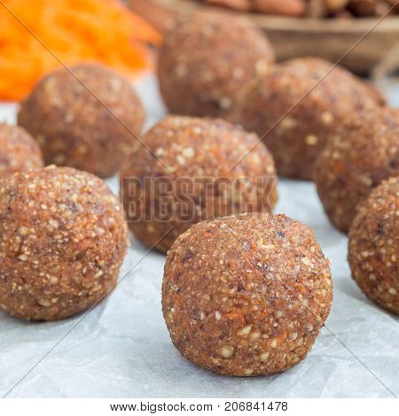 Healthy homemade paleo energy balls with carrot nuts dates and coconut flakes on parchment square format