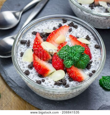 Chia seed pudding with strawberries almond and chocolate cookie crumbs on slate board square format