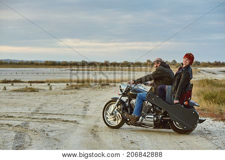 Young couple on a motorcycle in the countryside . Girl the musician with a guitar on a motorcycle