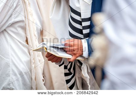 Hands and prayer book close-up. Orthodox hassidic Jews pray in a holiday robe and tallith.