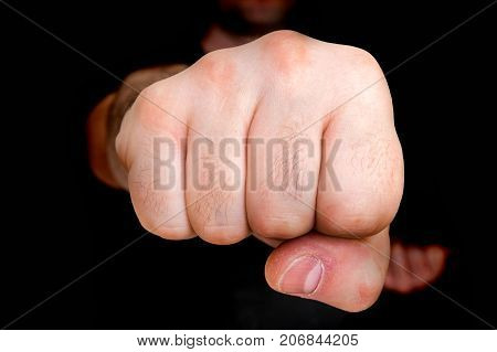 Young boxer showing punch a fist isolated on black - martial arts concept