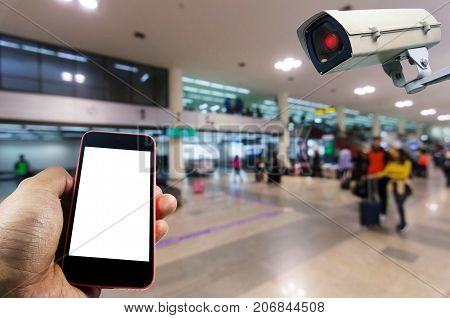 hand using smart phone monitoring and CCTV security indoor camera system operating in airport people transportation surveillance security and safety technology concept