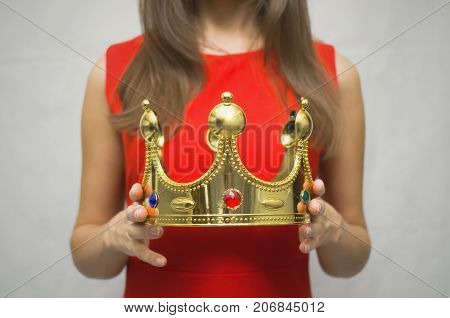 VIP client. Premium user concept. Success. Young woman in red dress holding in hands golden crown. Award ceremony. Top manager. Best employee of the year award.