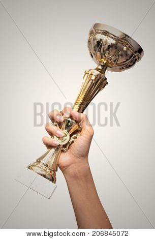 Golden cup award trophy in hand isolated on white background. Winner. Champion. First place award.