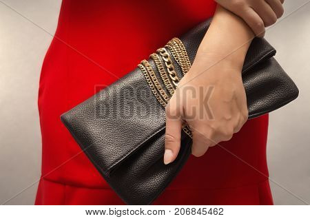Young woman in red dress with black leather clutch bag in her hands.