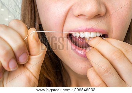 Woman Flossing Teeth With Dental Floss