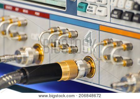 Measuring high-frequency equipment. Special high-frequency connectors are inserted into the instrument panel. Abstract industrial background.