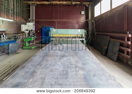 Wide steel sheet in front of old guillotine scissors. Sheet metal processing shop.