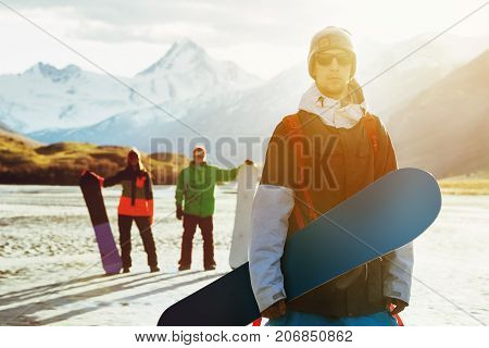 Three friends snowboarders posing on mountains backdrop. Snowboarding ski concept