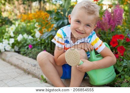A Cheerful, Suntanned Blond Boy Sits By The Flower Bed With Bright Flowers. Green Watering Can.