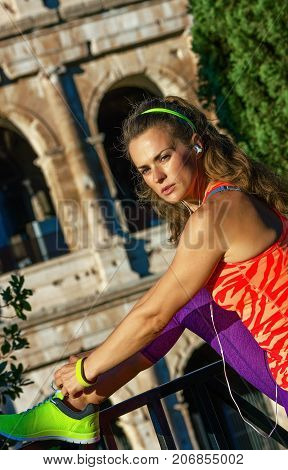 Fitness Woman Near Colosseum In Rome, Italy Tying Shoelaces