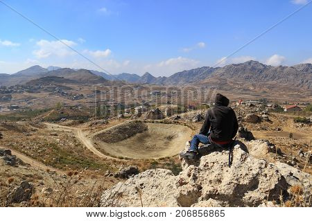 A man wearing a hoodie sitting on a rock with a view of a village underneath.