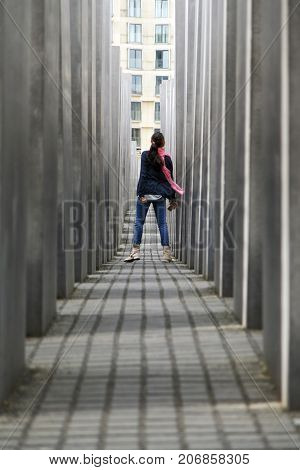Berlin, Germany: May 20, 2015: Memorial to the Murdered Jews of Europe. View along the pillars of the Holocaust Memorial in Berlin. A woman is walking through the maze.