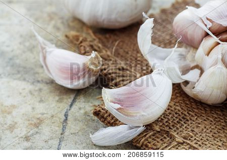 Garlic on cement floor and a sackcloth.