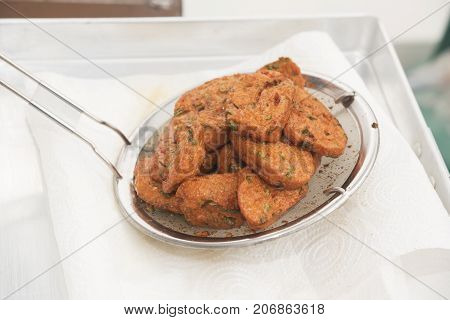 Cooked fried fish cakes in a ladle