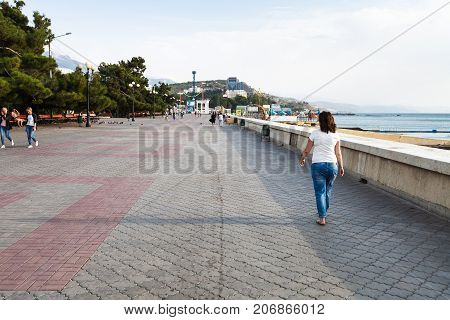 Tourists Walk On Embankment In Alushta In Morning
