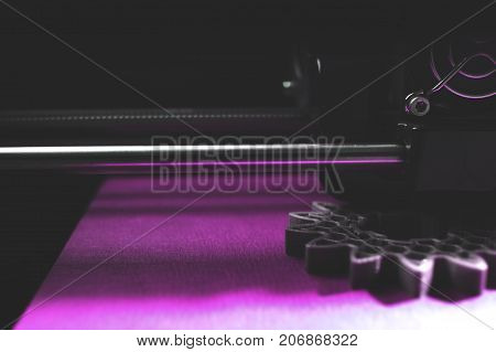 3D-printer manufacturing spur gears from silver-gray filament on blue print tape - dimmed part view on print head, print bed and object - magenta shade