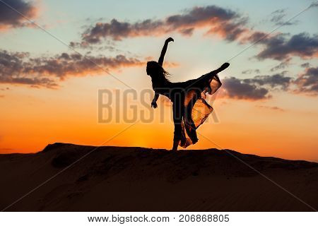 Dancing at night in the sand against the backdrop of the setting sun the silhouette of a dancer.