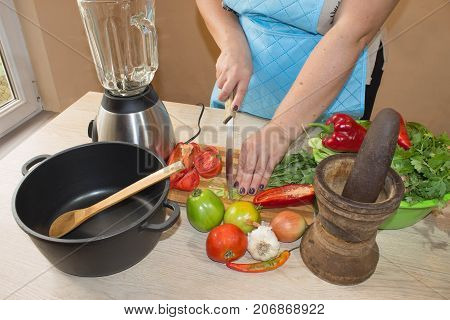 woman cooking healthy meal in the kitchen. Cooking healthy food at home. Woman in kitchen preparing vegetables. Chef cuts the vegetables into a meal. Preparing dishes