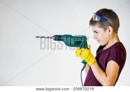 Portrait of young boy holding electric drill. Dreams of future profession. Smiling worker. Cheerful boy using electric drill.