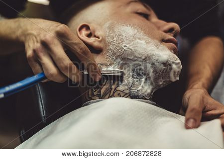 Crop barber using razor and shaving tattooed man in chair.