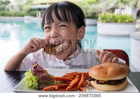 Asian Little Chinese Girl Eating Burger And Fried Chicken