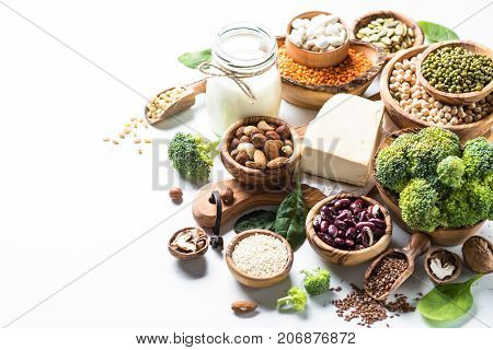 Vegan protein source. Tofu, vegan milk, beans, lentils, nuts, broccoli spinach and seeds on white table with copy space. Healthy vegetarian food.