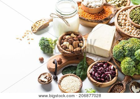 Vegan protein source. Tofu, vegan milk, beans, lentils, nuts, broccoli spinach and seeds on white table with copy space. Healthy balanced vegetarian food.