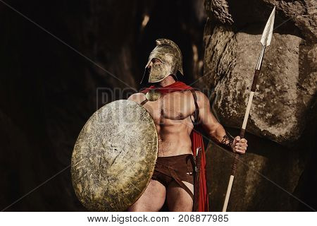 Muscular confident man in helmet and armor of ancient Roman warrior holding spear and shield looking confidently away on nature. Spartan. poster