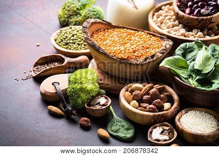 Healthy vegan food assortment. Leguminous, nuts, broccoli, spinach  and seeds on dark rusty table with copy space.