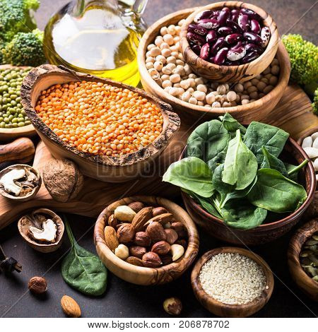 Healthy vegan food assortment. Leguminous, nuts, broccoli, spinach and seeds on dark rusty table. Square.