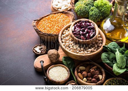 Healthy vegan food assortment. Leguminous, nuts, oil, broccoli, spinach and seeds on dark rusty table.