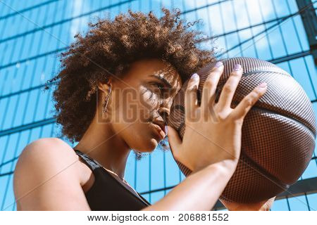African-american Woman Adjusting Aim With Basketball