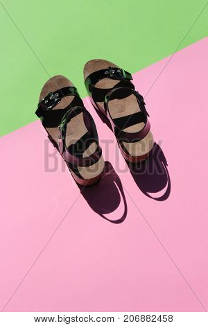 Top view of trendy black sandals on pastel background.