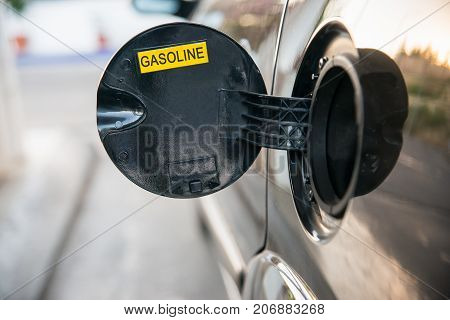Opened car fuel tank with the word gasoline. Copy space for text