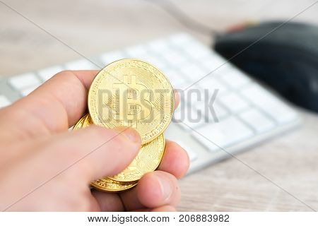 Several golden bitcoins in a hand near white keyboard and computer mouse. Electronic money mining concept