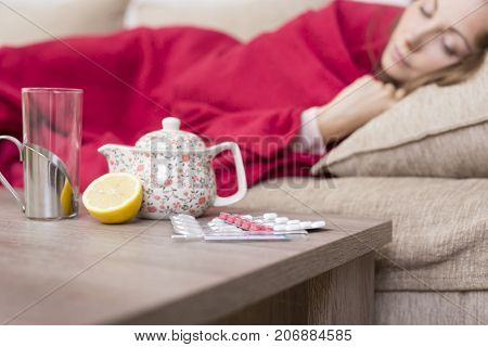 Sick woman covered with a blanket lying in bed with high fever and a flu. Pills teapot and lemon on the table. Selective focus on the pills