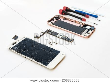 Disassembled cracked smartphone screen preparing to repair or replace new screen on white background